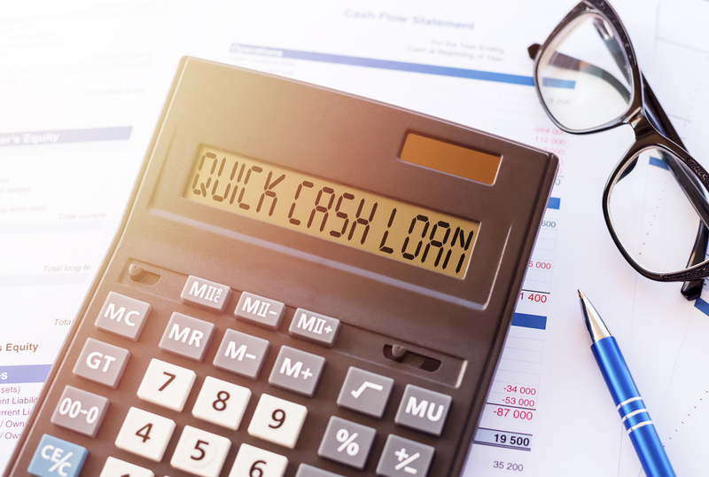 'QUICK CASH LOAN' spelt out on the display of a desk calculator