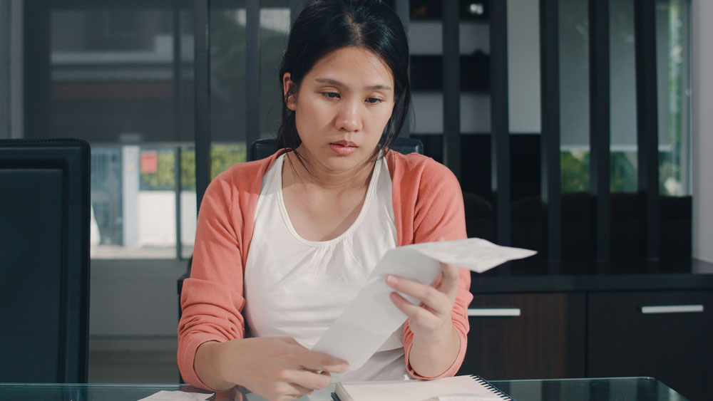 Distraught young woman sitting at a table looking at her bills