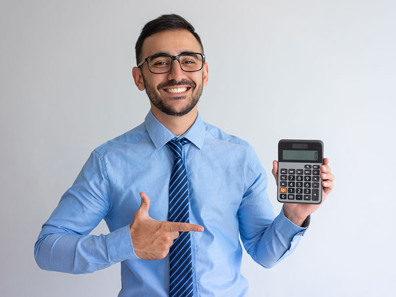 Smiling young man in office attire pointing at a calculator he is holding