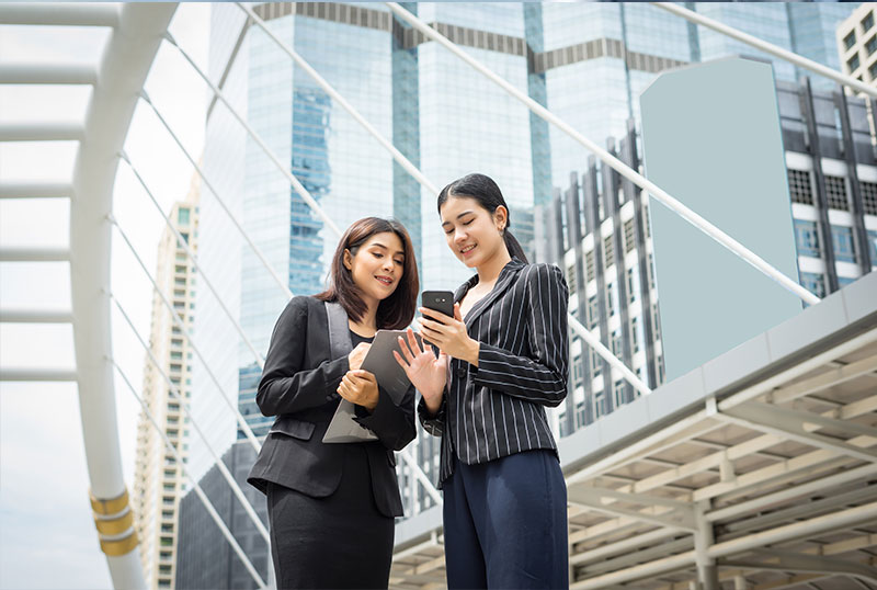 2 young women in office attire looking at a phone screen outside an office building
