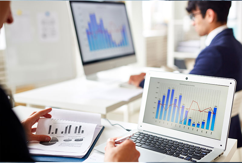 Young man and woman work on desktop and laptop looking at charts and printouts