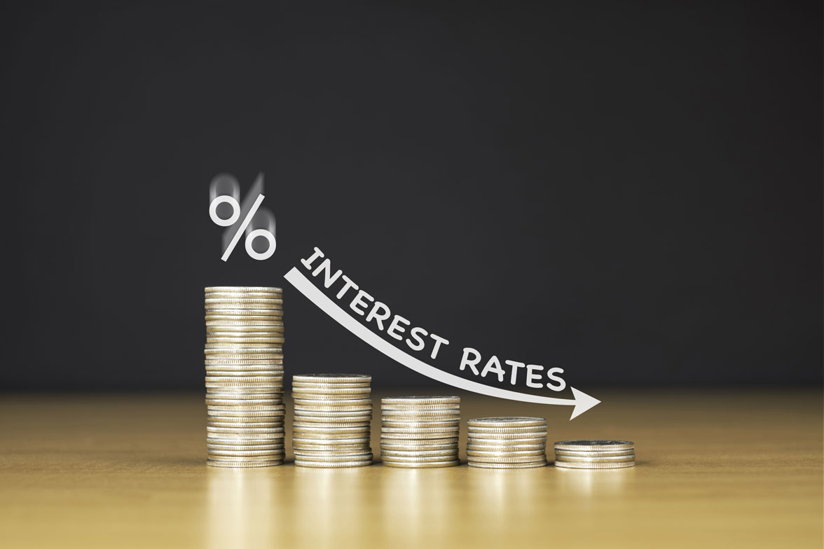 A graph arrow shows reducing interest rates plotted against coins, reaching the lowest interest rate