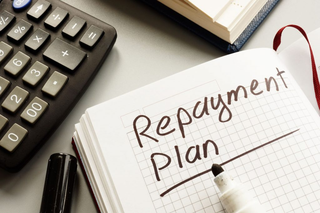 The words Repayment Plan written on a notebook, and calculator on desk beside it as lowest interest rates are being searched for