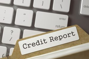 """Against a Mac keyboard, a folder with a label that reads, """"credit report"""", depicting free credit report Singapore"""